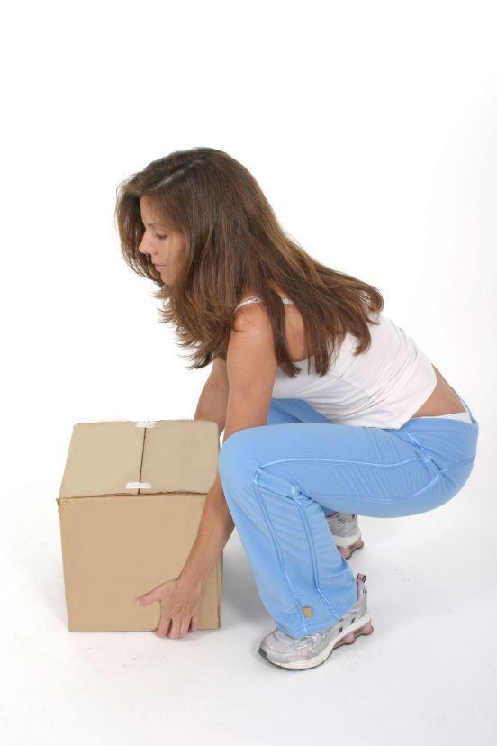 Kvinne demonstrerer rett løfteteknikk: bøyde bein, men ikke bøyd rygg. Foto.