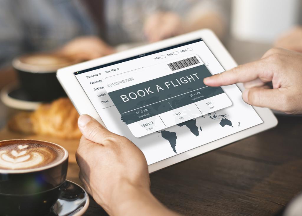 Online booking av reise på tablet. Foto.