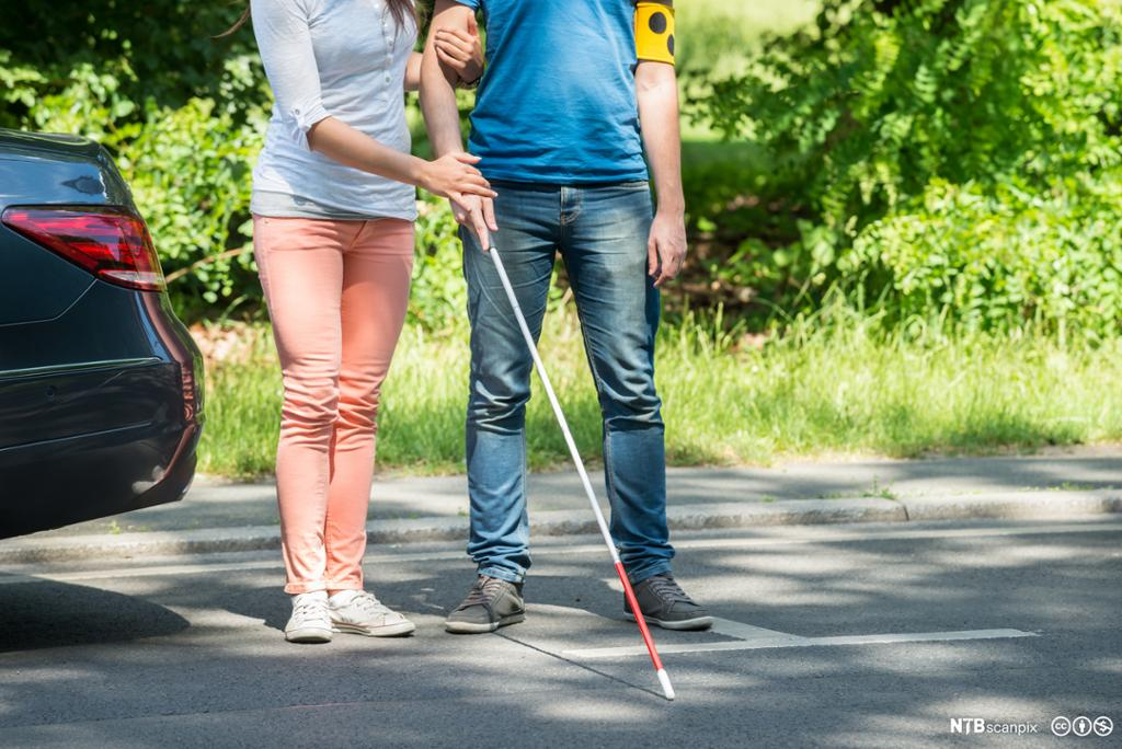 Kvinne assisterer blind mann med hvit stokk. Foto.