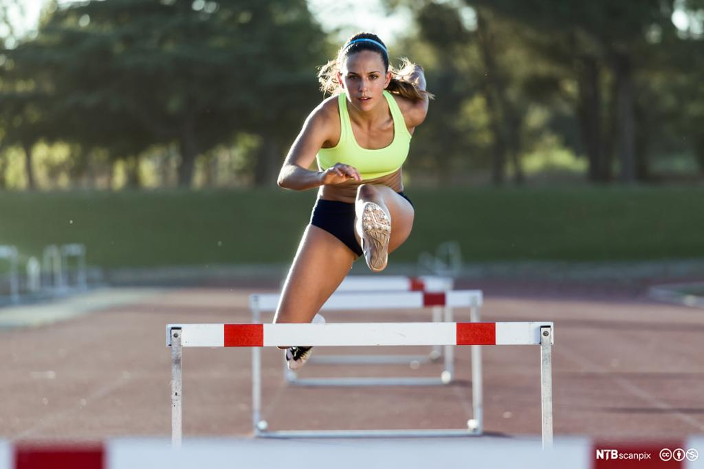Jente løper 100 meter hekk. Foto.