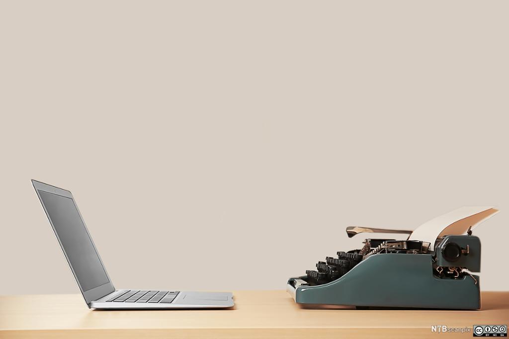 Bilde av en moderne laptop og en gammel skrivemaskin. Foto.