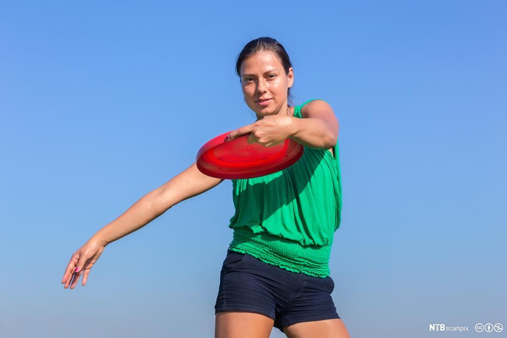 Kvinne som kaster frisbee. Foto.