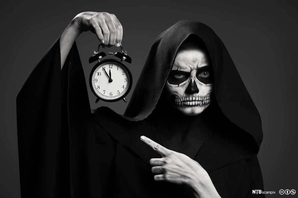 Mørk skikkelse som symboliserer døden holder klokke som viser fem på tolv. Foto.