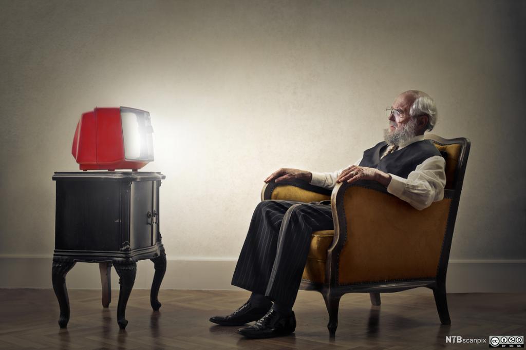 En gammel mann sitter i en stol er ser på er rødt plastikkfjernsyn. Foto.