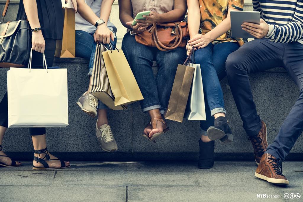 Gruppe mennesker som sitter på en kant med mange handleposer i hendene