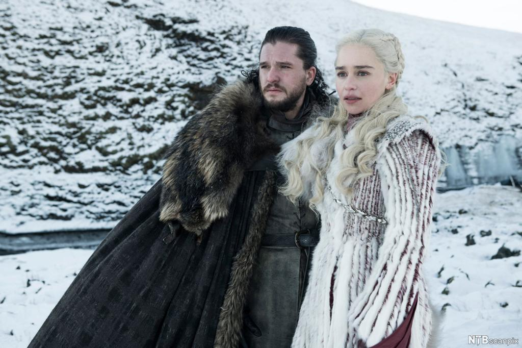 John Snow og Daenerys Targaryen står framfor eit snødekt fjell og ser bekymra mot venstre. John har svart hår, svart heilskjegg og lang, svart pelskappe. Daenerys har langt, kvitt hår og er kledd i kvitt. Foto.