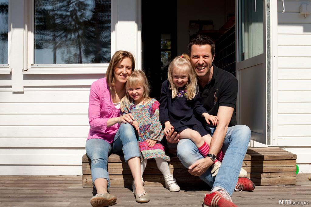 Mor, far og to barn sitter smilende på trappa utenfor et hus. Foto.
