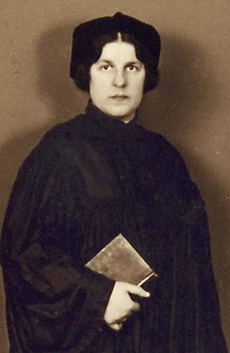 Portrett av kvinne i sort kappe. Holder en bok. Foto.