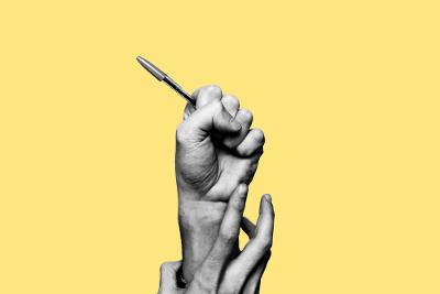 En hånd med penn blir dradd ned av en annen hånd. Gul bakgrunn. Foto.