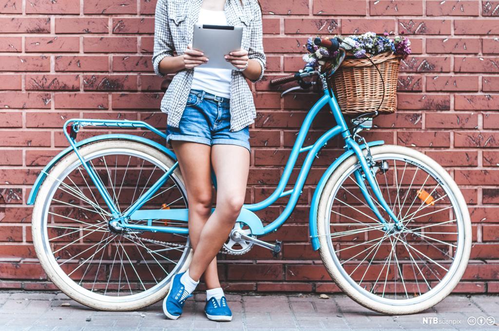 Jente som står ved en parkert sykkel. Foto.