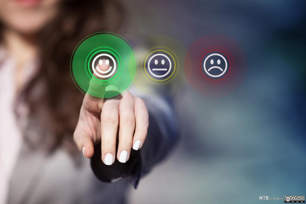 Kvinne trykker på et smilefjesikon på en virtuell berøringsskjerm. Foto.