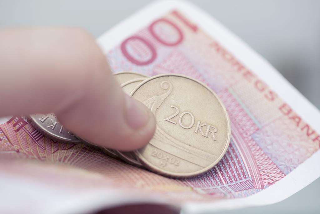 Hånd som holder i norske mynter og sedler. Foto.