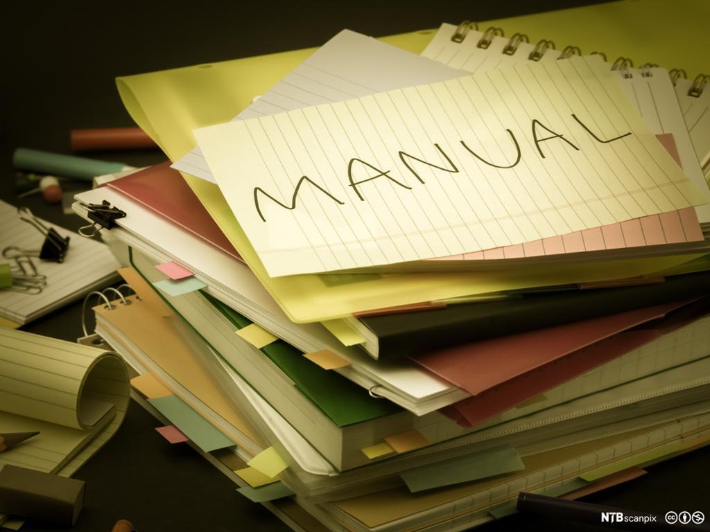 Store bunke med dokumenter, det øveste er merket med manual. Foto.