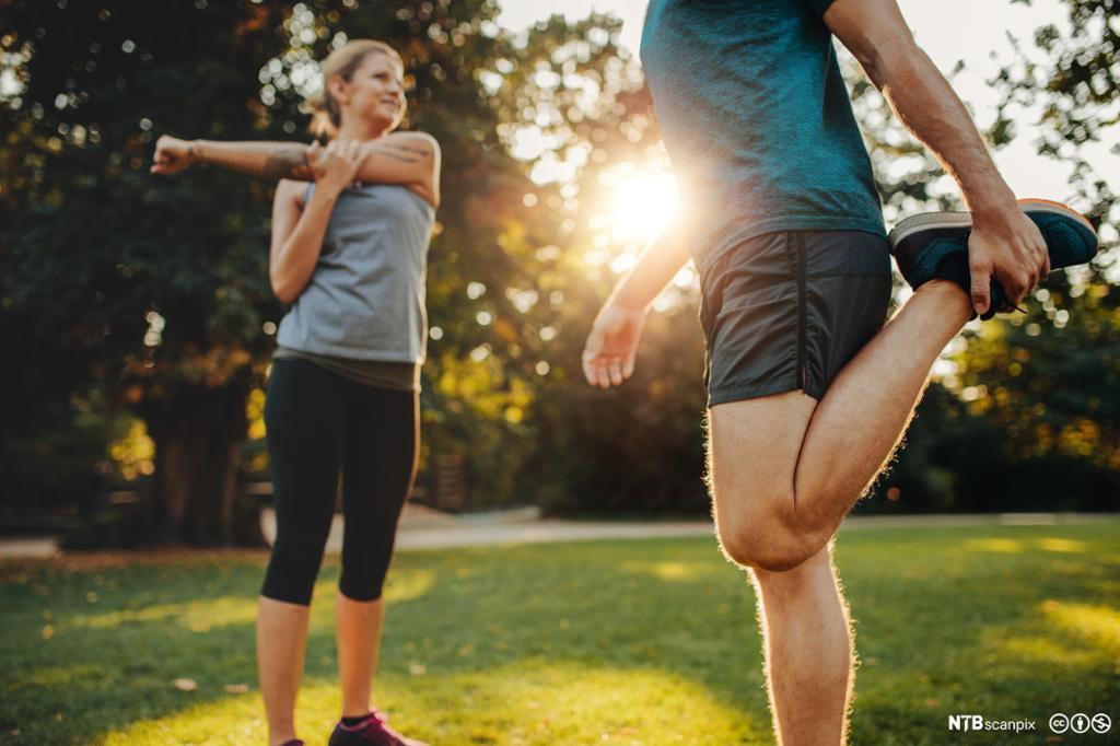 Ung mann og kvinne gjør oppvarmingsøvelser i parken. Foto.