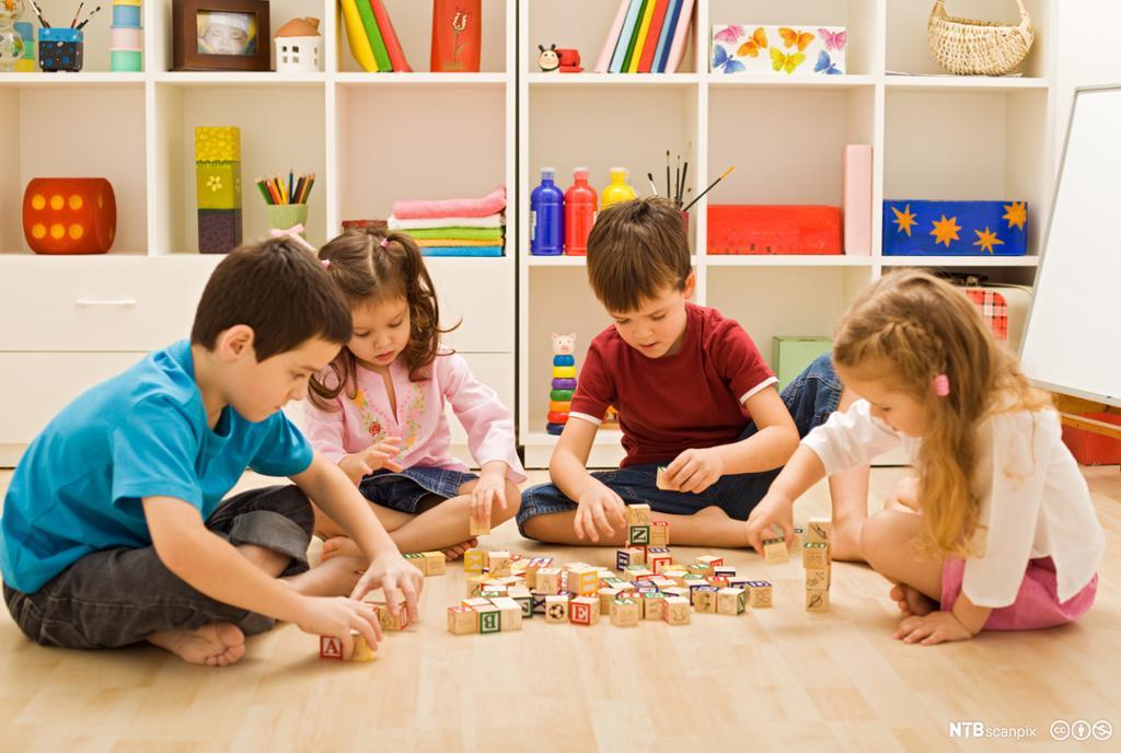 4 barn som leker med klosser. Foto.