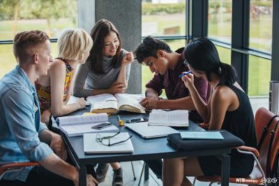 Ungdommer sitter rundt et bord og samarbeider om skolearbeid. Foto.