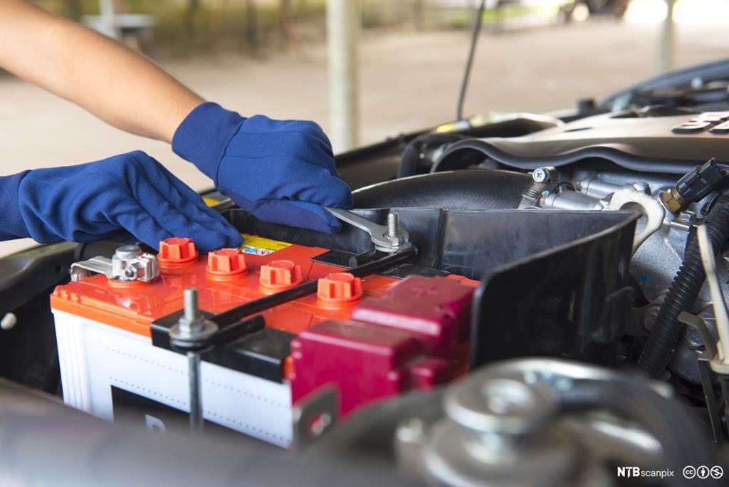 To hender justerer bilbatteri. Foto.