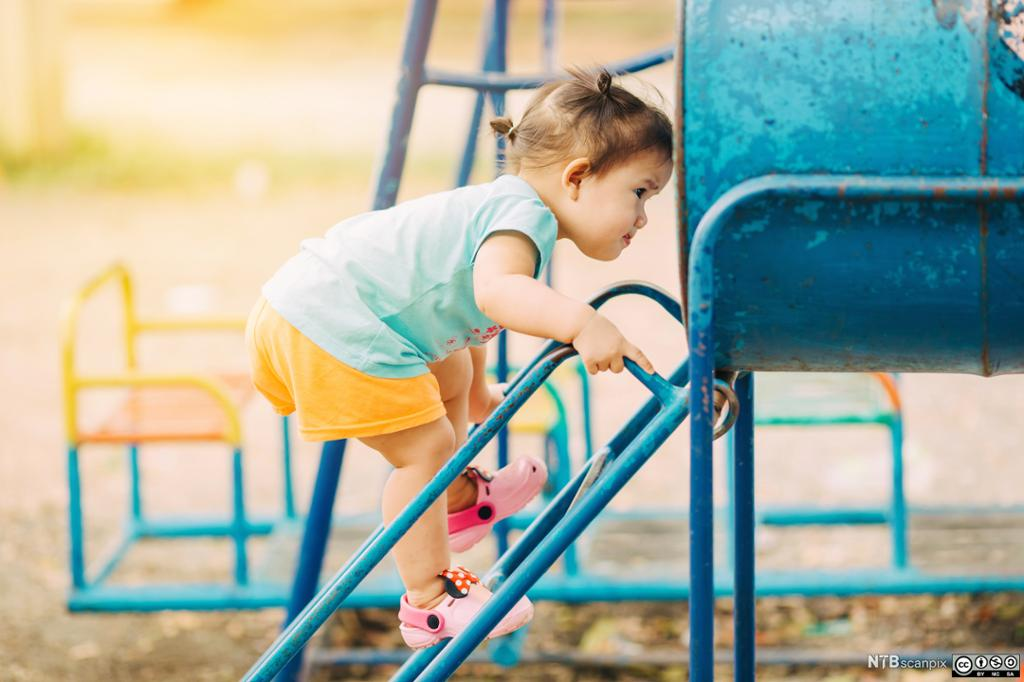 En liten jente øver på ferdighetene sine i en lekepark. Foto.