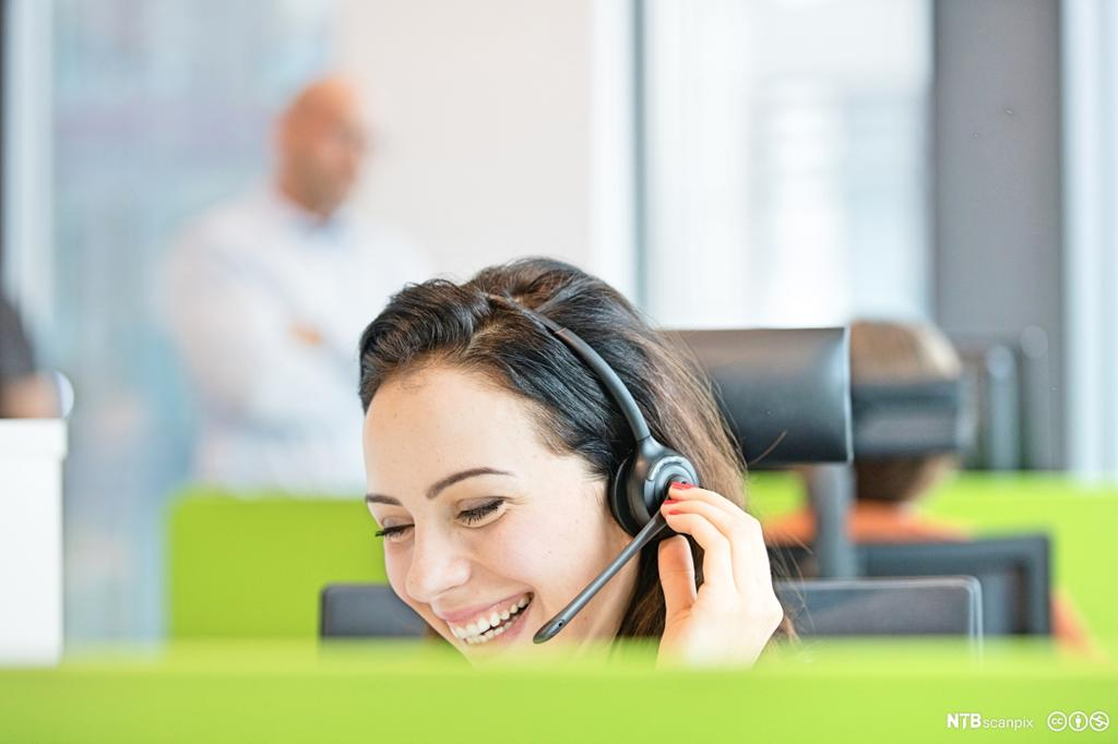 Forretningskvinne med headset smiler. Bilde.