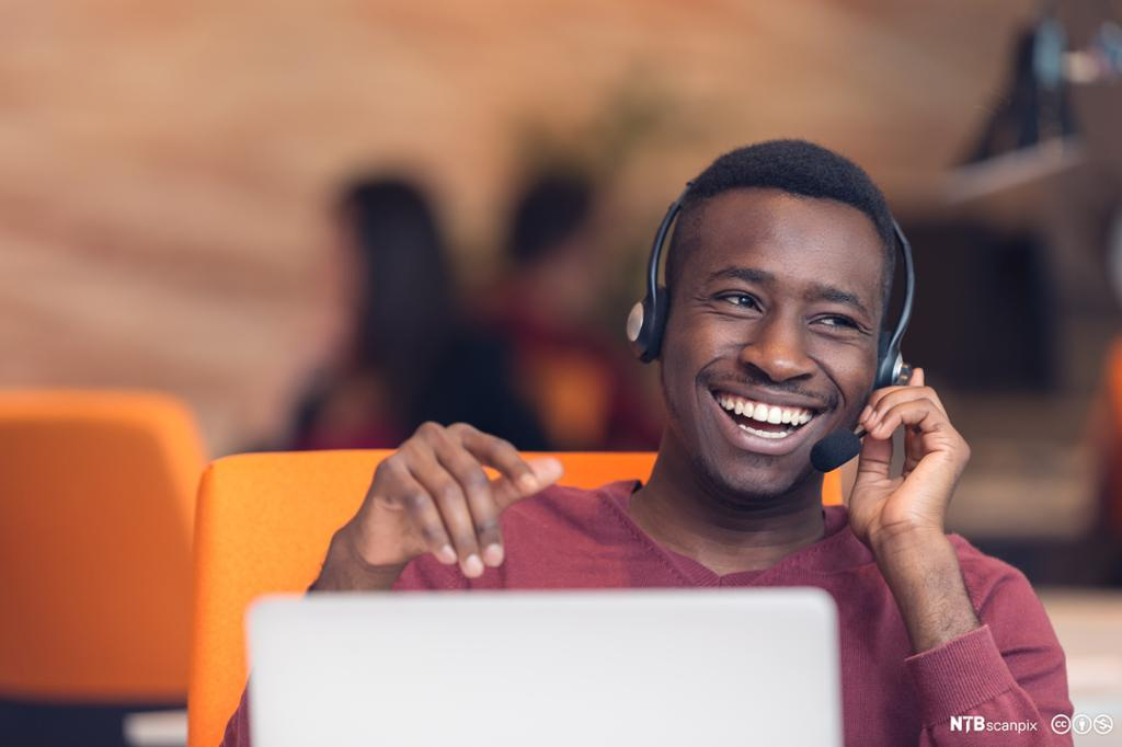 Smilende mann med headset foran en åpen pc. Foto.