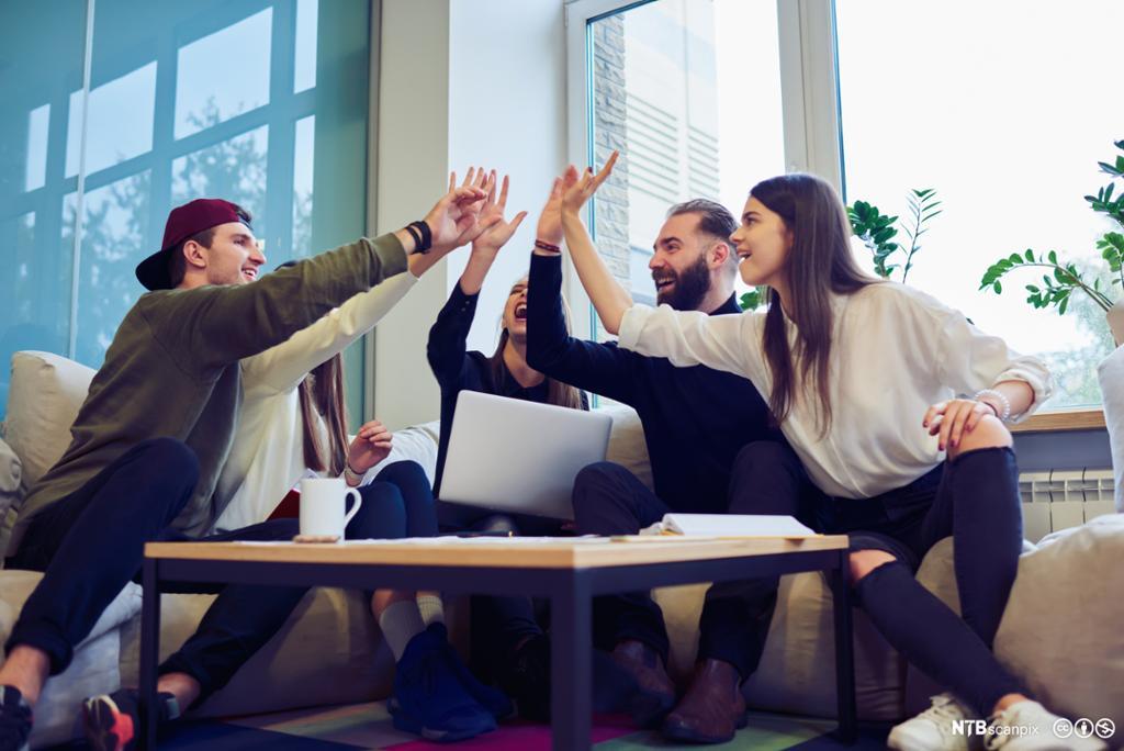 Smilande unge menneske som sit rundt eit bord og gir kvarandre high five. Foto.