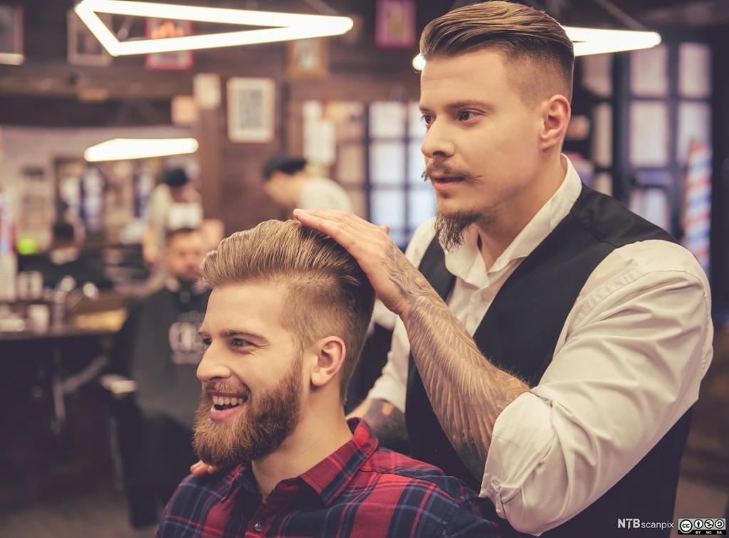 Smilende mannlig kunde hos frisør. Foto.