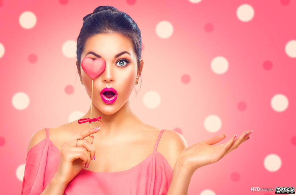 Kvinne i rosa holder hjerteformet kjærlighet på pinne. Foto.