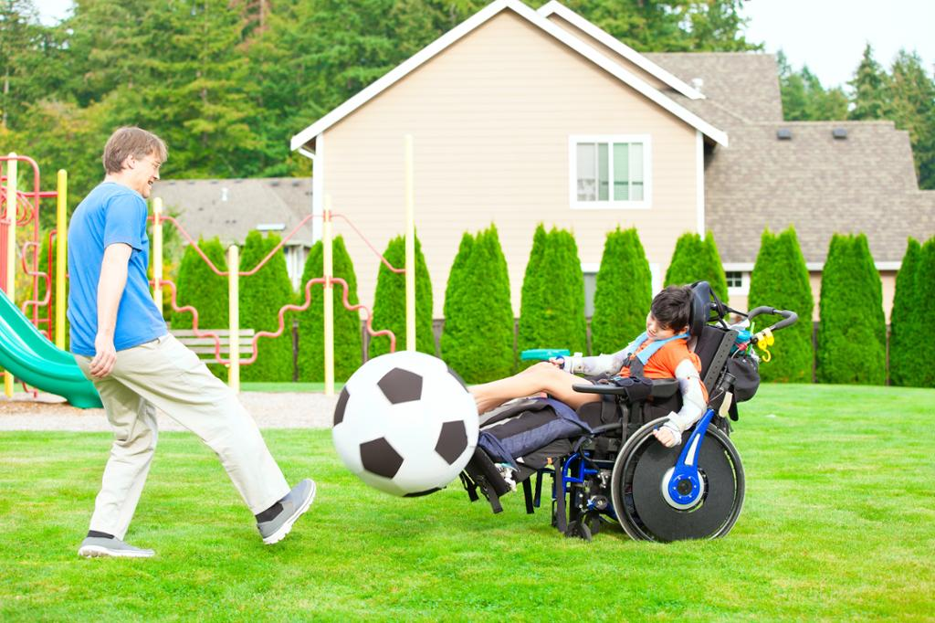 Voksen mann og barn i rullestol spiller fotball med stor plastball på gresset. Foto .
