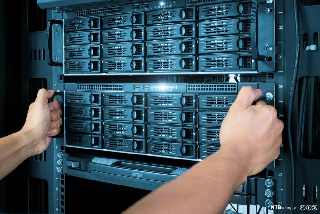 Hender drar ut nettverkstilkoblet lagring (NAS) fra et rack skap. Foto.