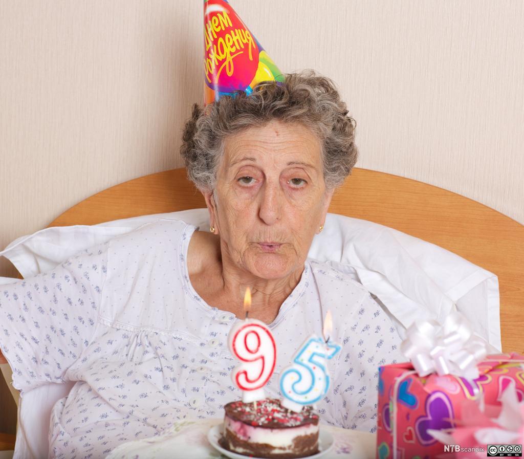 Gammel kvinne som er festpyntet og sitter med en stor bløtkake foran seg. Foto.