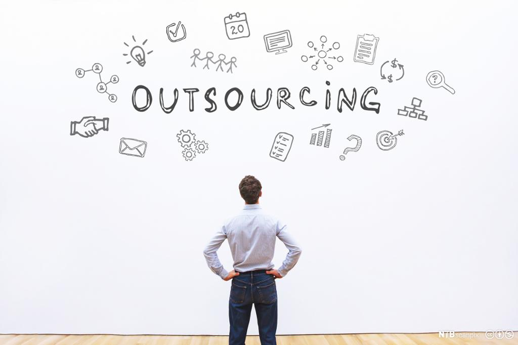 Mann står og studerer en vegg hvor det er tegninger og teksten Outsourcing. Bilde.