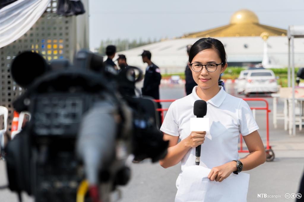 Kvinnelig reporter foran kamera. Foto.