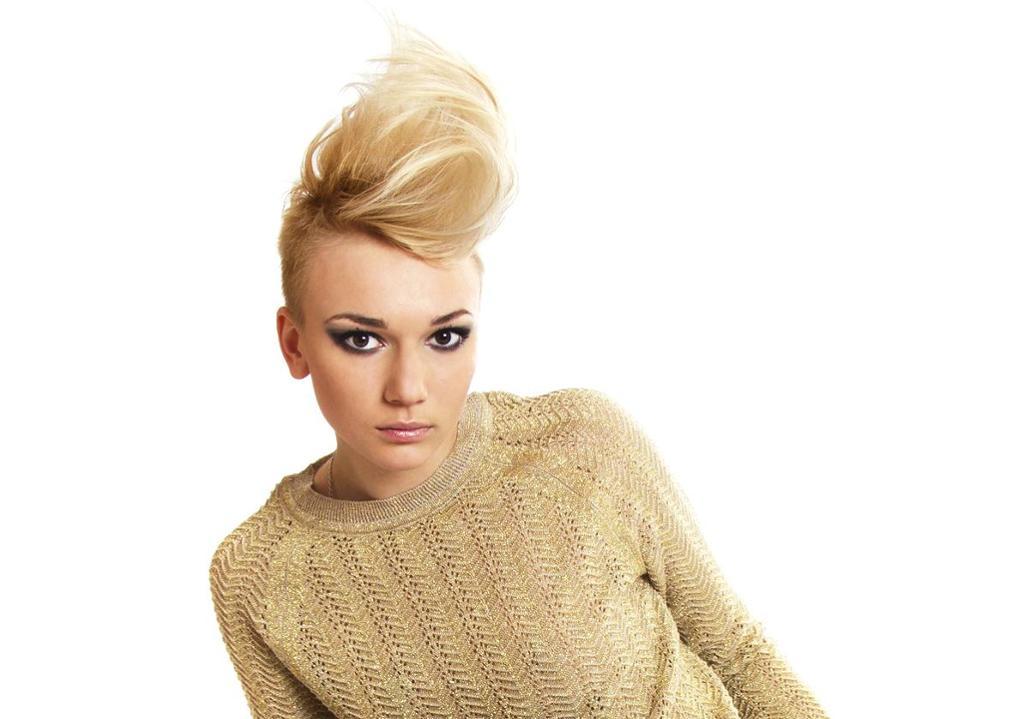 Kvinne med helt kortklipt hår på sidene og mye hår på toppen som er stylet til å stå opp. Foto.