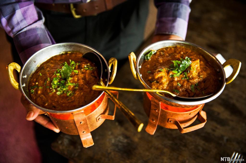 En person holder indisk mat i to gryter. Foto.