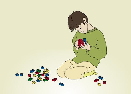 bildet viser en gutt som sitter på gulvet å leker