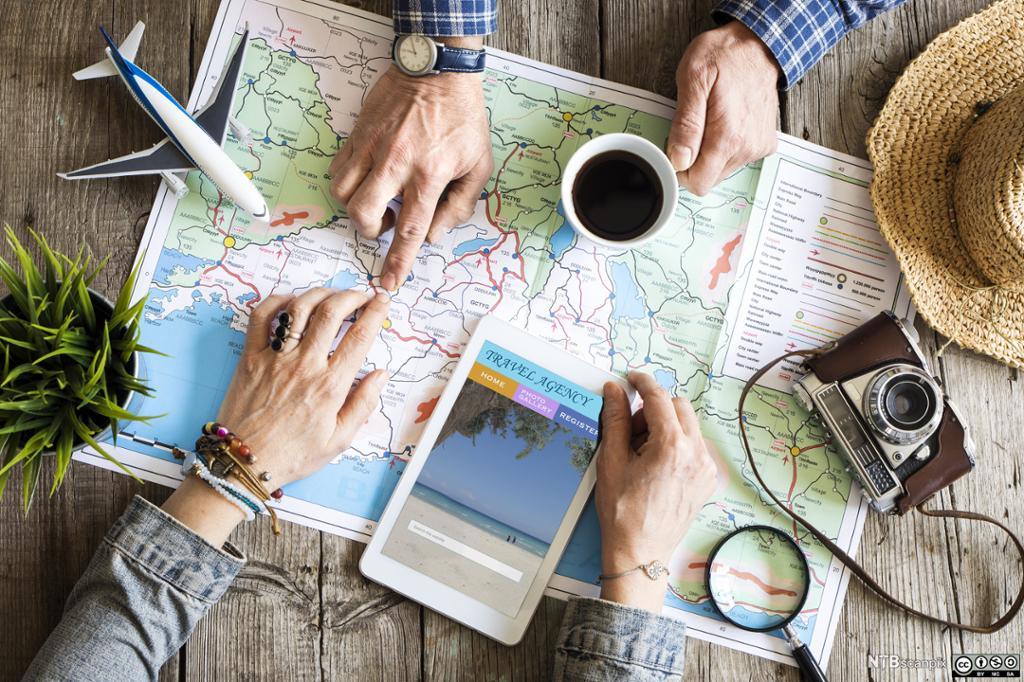 Oversiktsbilde som viser reiseeffekter og et tre personer som sitter rundt et kart.
