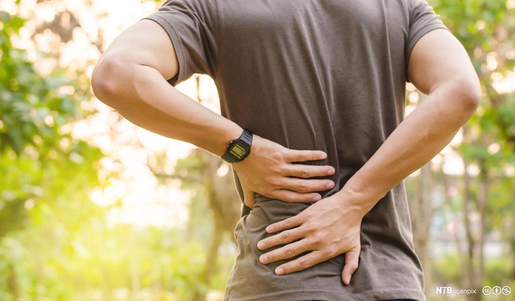Mann tar seg til ryggen med smerter. Foto.