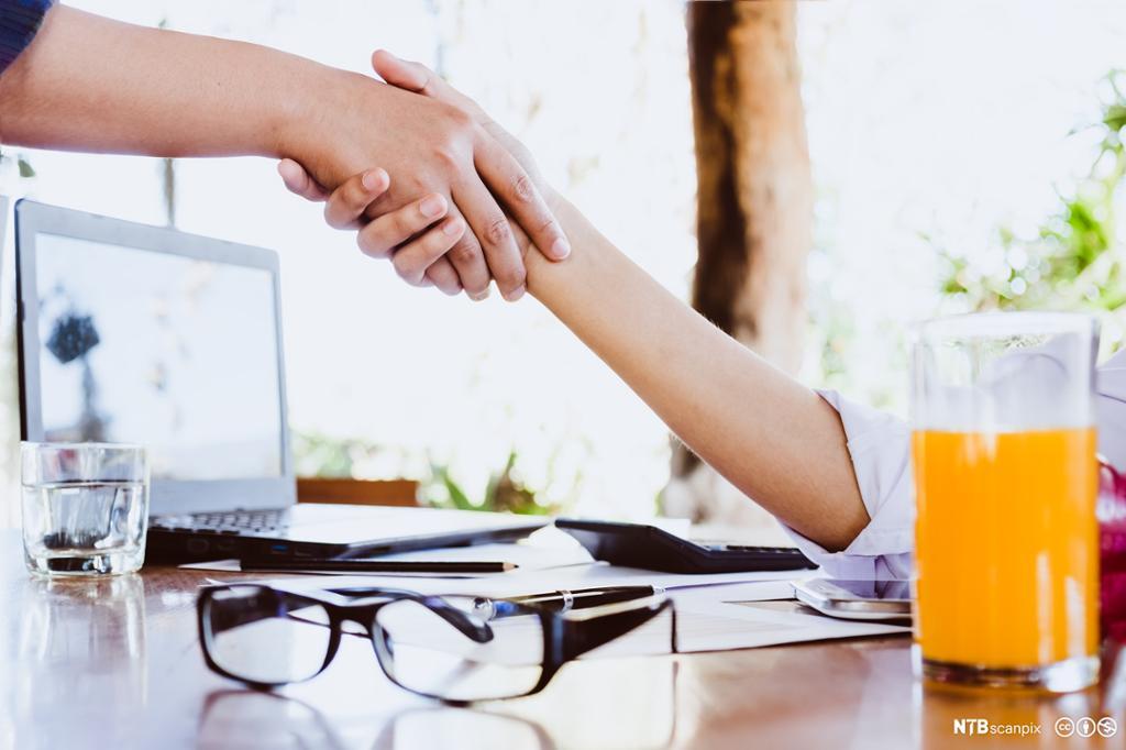 To kvinner gir hverandre et håndtrykk på et kontor. Foto.