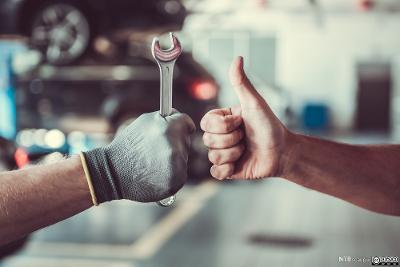 Mekaniker holder en skiftenøkkel og får tommel opp. Foto.