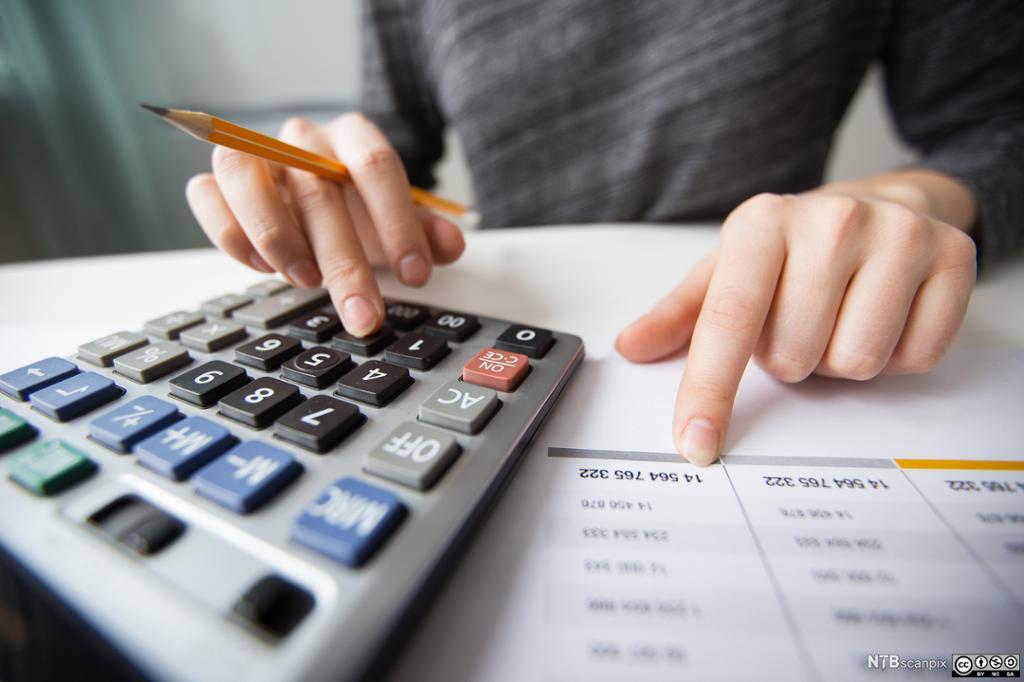 Nærbilde av fingre som taster inn tall på en kalkulator. Foto.