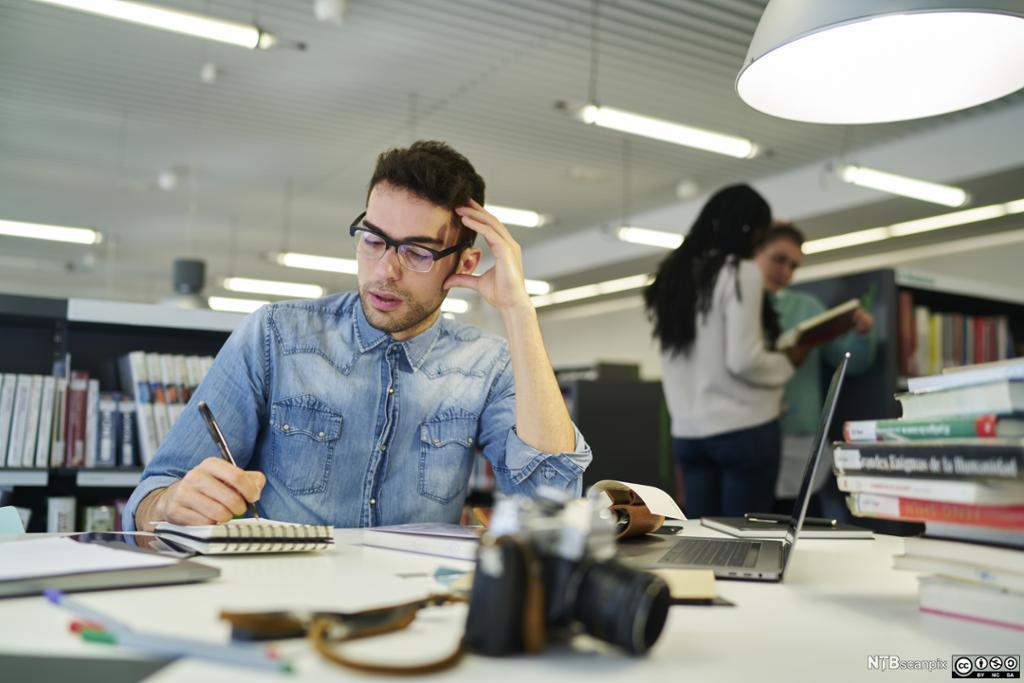 Ung mann jobber i kontorlandskap. Foto.