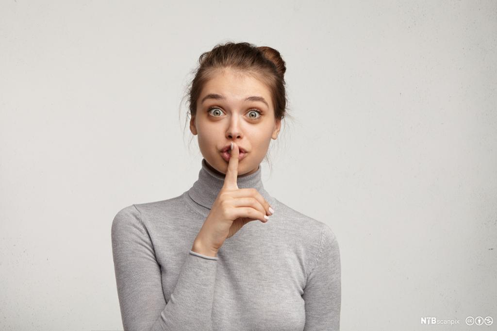 Kvinne som viser hysjtegn foran munnen. Foto.