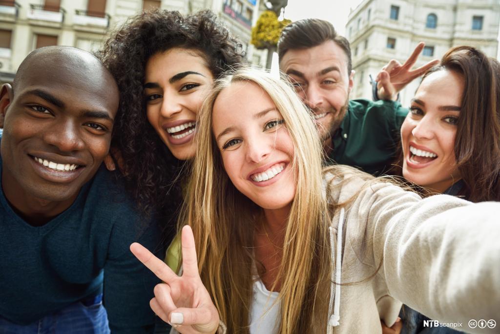 Multikulturell ungdomsgruppe tar selfie. Foto.