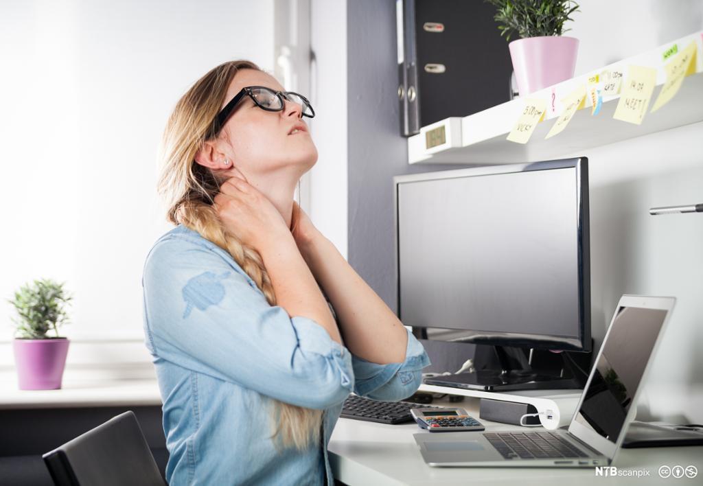 Kvinne på hjemmekontor lider av nakkesmerter. Foto.