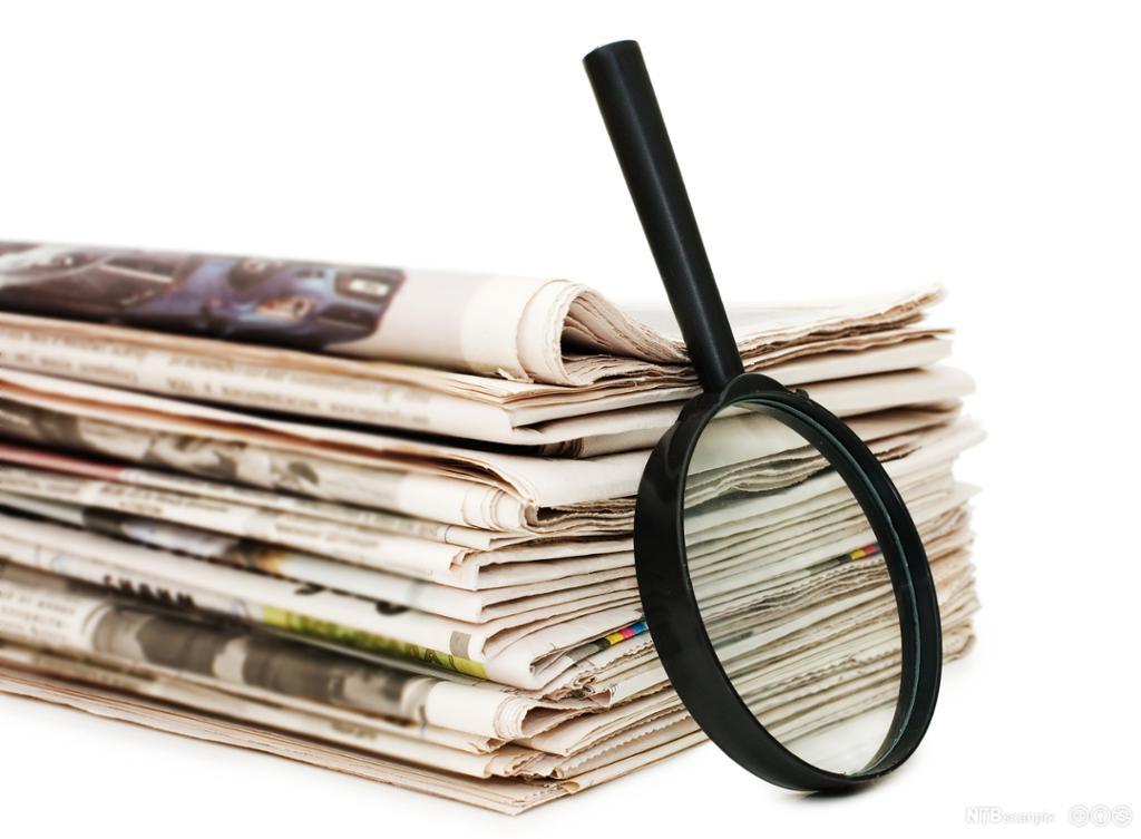 Forstørrelsesglass lent opp mot en bunke aviser