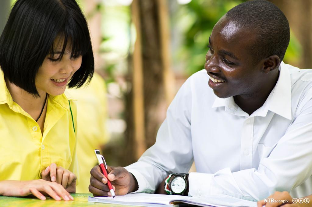 Ung afrikansk mann snakker med asiatisk jente. Foto.