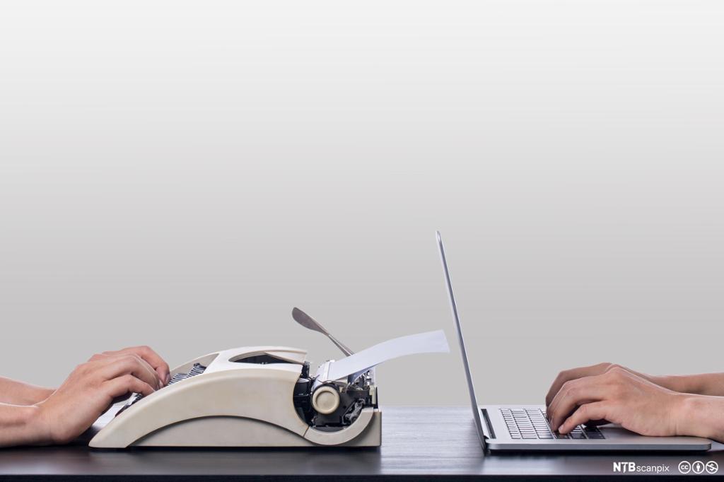 Bærbar og skrivemaskin mot hverandre på bordet. Foto.