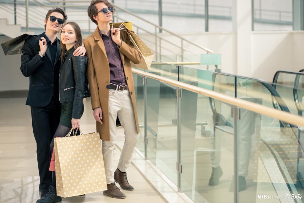 En jente og to gutter med handleposer i hendene på et kjøpesenter