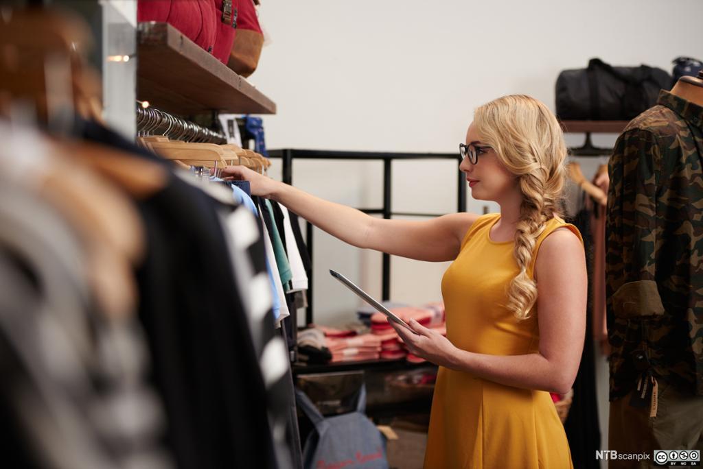 Bilde av en kvinne som inspiserer en kjole utstilt i et showroom av den israelskfødte designeren Elie Tahari i New York.