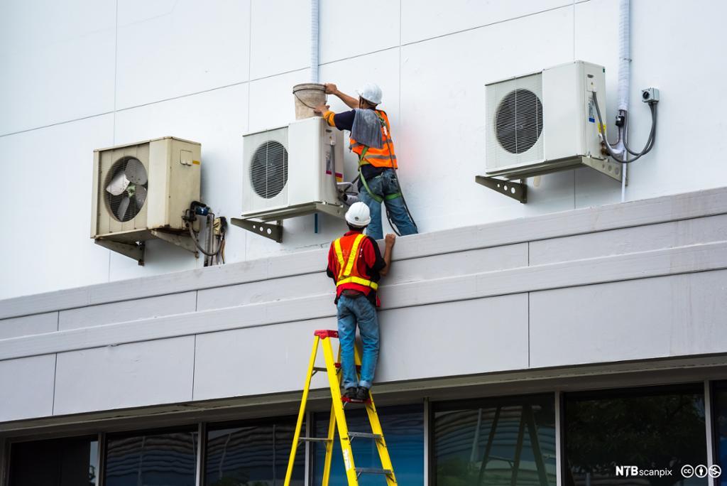 To menn installerer varmepumper. Foto.